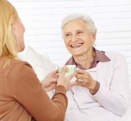Familie mit Seniorin trinkt Kaffee